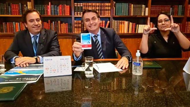 Bolsonaro segurando uma caixa de hidroxicloroquina em live na noite de 9 de abril, ao lado do presidente da Caixa, Pedro Guimarães, e de uma intérprete de libras. / Imagem retirada do site Gazeta do Povo.